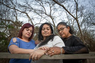 From Left, Delia Ramos, Betty Fuentes, and Ana Flores embrace in prayer in Harlingen on March 11, 2021.