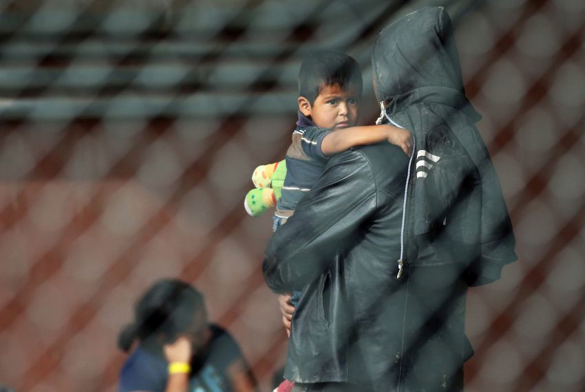 A migrant holds a small child inside a holding area under the Paso Del Norte International Bridge before being taken to processing facilities in El Paso.