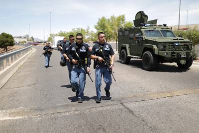 Law enforcement officers and an armored vehicle were on the scene near a Walmart in El Paso after a mass shooting Saturday.