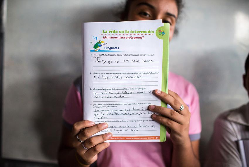 "A student presents her answers to gang related questions in an El Salvador elementary school workbook. ""What have you hear..."