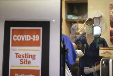 A nurse demonstrates to a student how to self-administer a COVID-19 test a at a testing location at the University of Texas at Austin. Sept. 4, 2020.