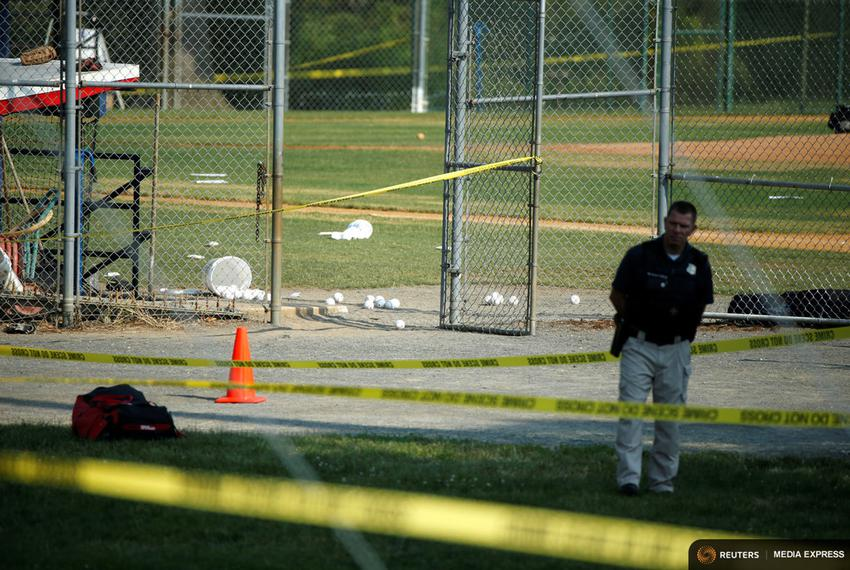 A police officer mans a shooting scene after a gunman opened fire on Republican members of Congress during a baseball practi…