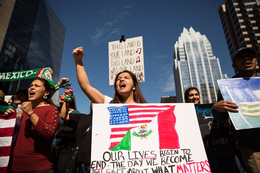 """Klevelin Lion chants at the front of the """"Day Without Immigrants"""" march on Congress Avenue, Feb. 16, 2017, in Austin, TX."""