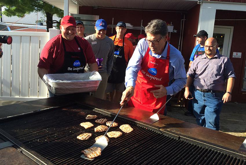 Rick Perry flips pork on a grill Tuesday at the Iowa State Fair in Des Moines, Iowa.