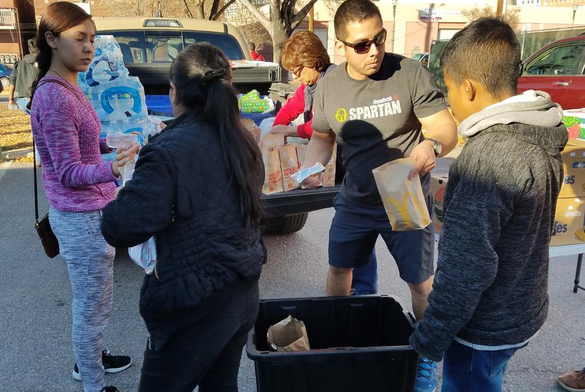 Javier Grajeda hands out hamburgers to asylum-seeking migrants who were released by ICE on Christmas Eve in El Paso, Texas.