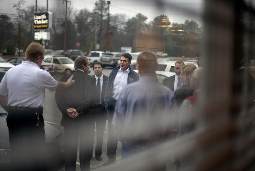Republican presidential candidate, Texas Gov. Rick Perry greets supporters as he arrives for a campaign stop at Lizard's Thi…