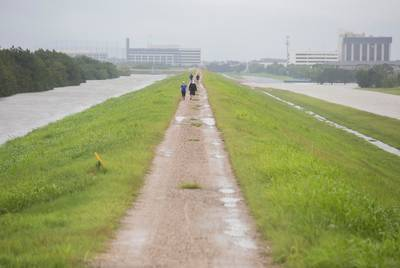 People walk along the Barker Reservoir Dam in Houston on Tuesday, Aug 29, 2017. Torrential rains from Hurricane Harvey caused the U.S. Army Corps of Engineers to release water from the reservoir, aggravating flooding in neighborhoods below the dam.