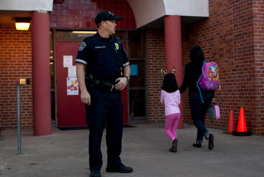 Austin Police Officer Cory Ehrler monitors the entrance to Ridgetop Elementary School after classes start on the Monday foll…