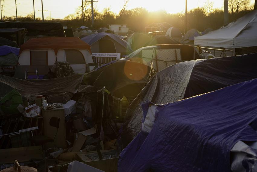 The sun sets over the tops of tents at a homeless encampment on state-owned land in Austin on Jan. 18, 2021.
