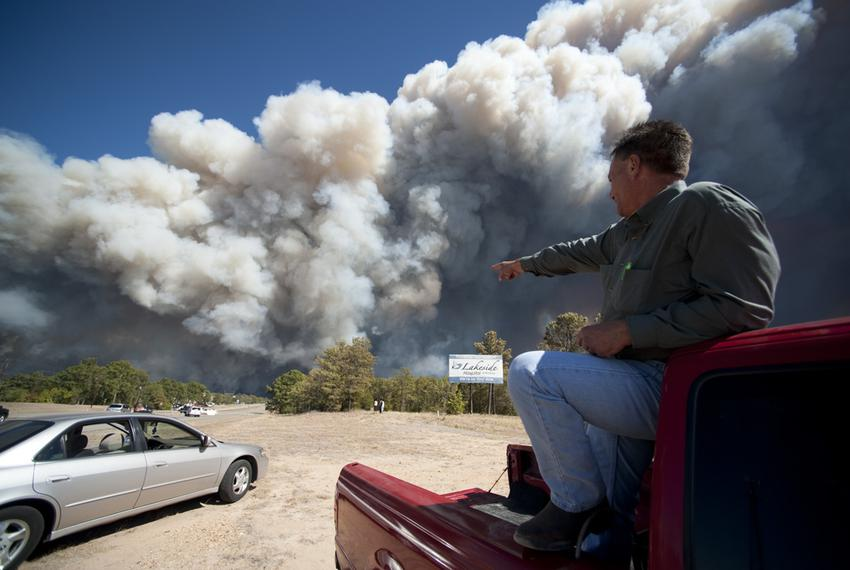 A Bastrop resident points to flames as smoke billows over Texas 71 in Bastrop Country during the wildfires on September 5, 2…
