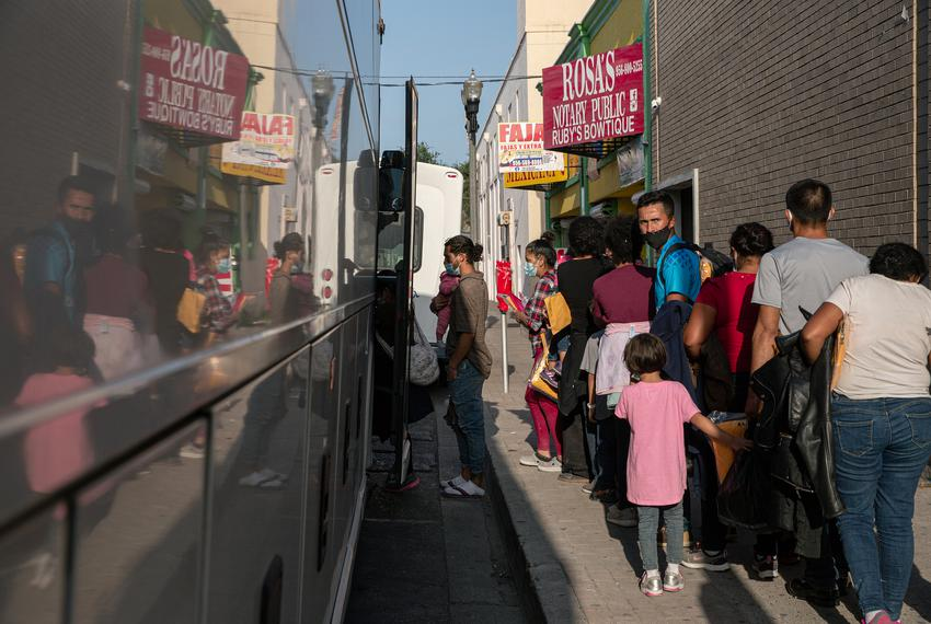 A group of migrants wait to board a charter bus in front of the Catholic Charities RGV Humanitarian Respite Center in McAlle…