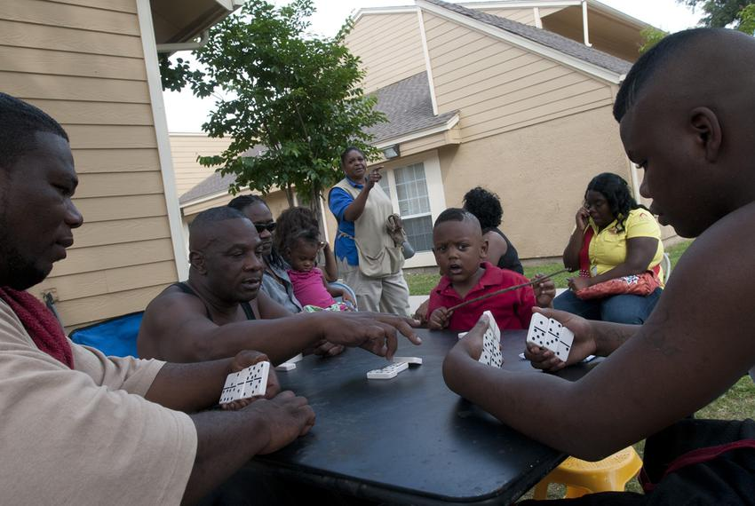 Robert Johnson (far left), Larry Williams (second from left), and DeNarious Scales (far right) play dominoes outside the Whi…