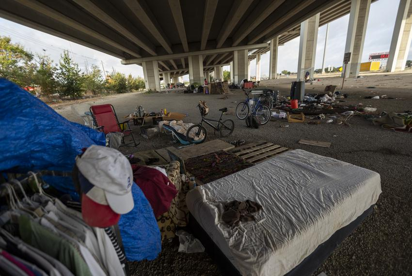 An encampment site under the TX-71 and W. Ben White Blvd. overpass in Austin. Wind has blown belongings and trash across the…