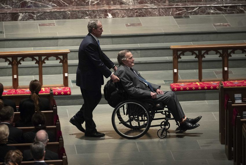 Former President George W. Bush leads his father, former President George H.W. Bush, into the funeral service at St. Martin's Episcopal Church in Houston for the funeral service of former First Lady Barbara Bush, on April 21, 2018.
