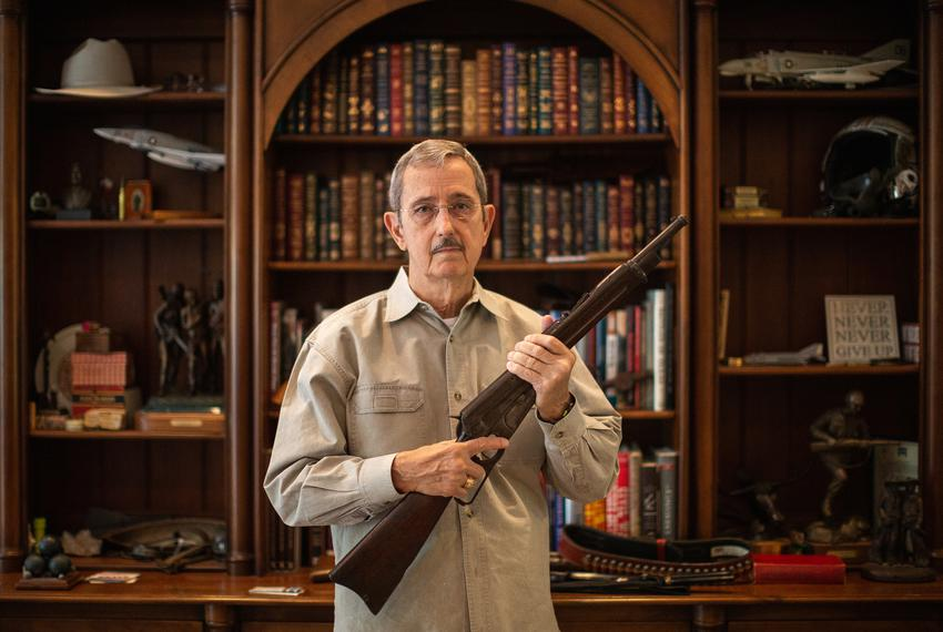 Former Land Commissioner  and State Sen. Jerry Patterson holds up a Winchester Model 1895 carbine, a model favored by the Te…