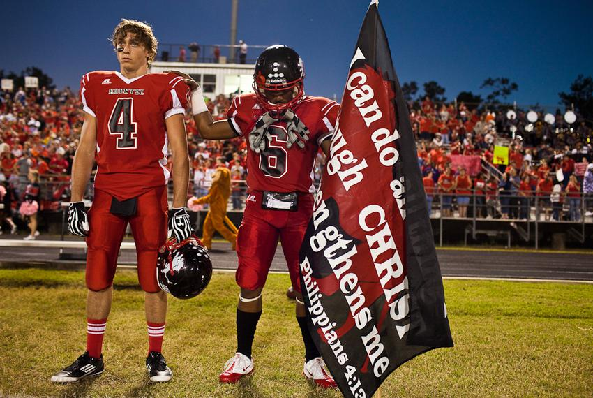 As two Kountze football players prepare to play a game on Oct. 5, 2012, one holds a banner with a Bible verse. A Hardin Coun…