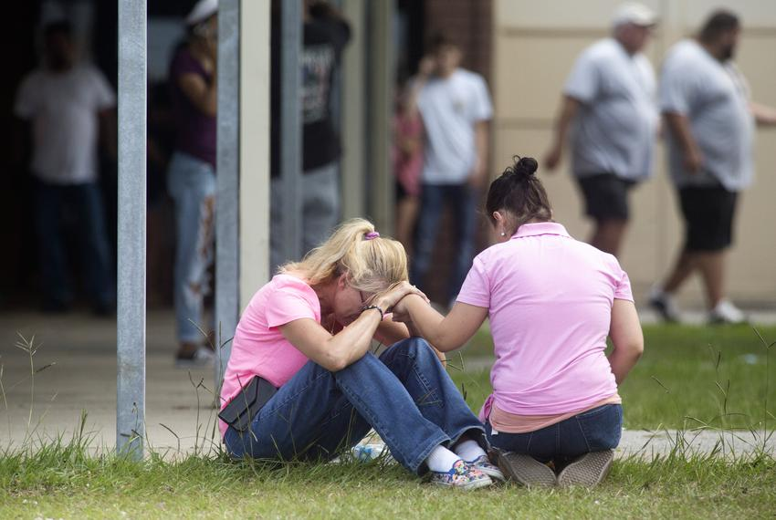 People outside a middle school set up as a reunion point for parents and students in Santa Fe, Texas on Friday, March 18, ...