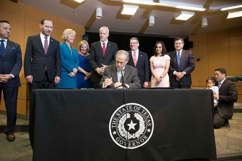Gov. Greg Abbott signs several bills reforming Child Protective Services in a ceremony with state legislators at the Department of Family and Protective Services headquarters onMay 31, 2017.