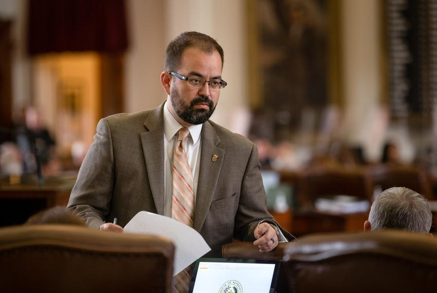 State Rep. Joe Moody, D-El Paso, speaks with colleagues on the House floor during session at the state capitol on May 25, 20…