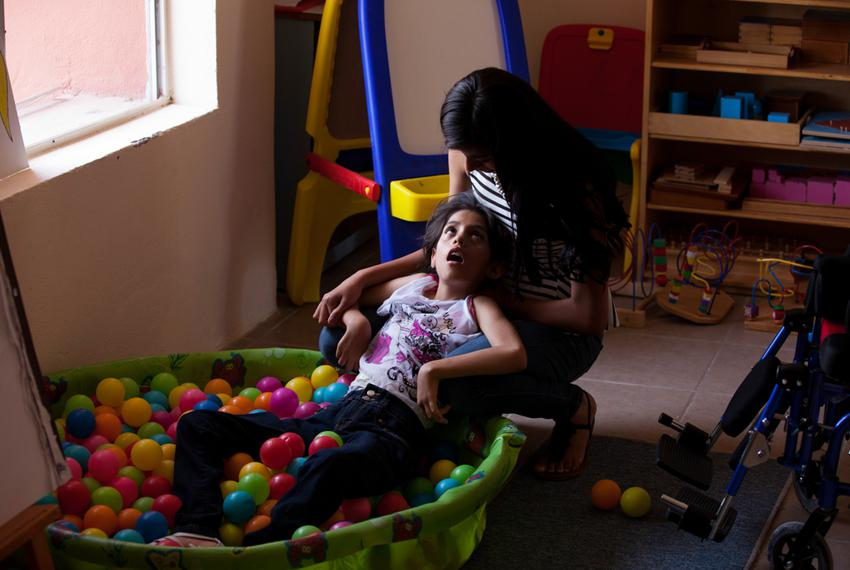 A worker provides therapy to a paralyzed 12-year-old girl at the Los Ojos de Dios Center in Ciudad Juárez, Mexico on June 3,…