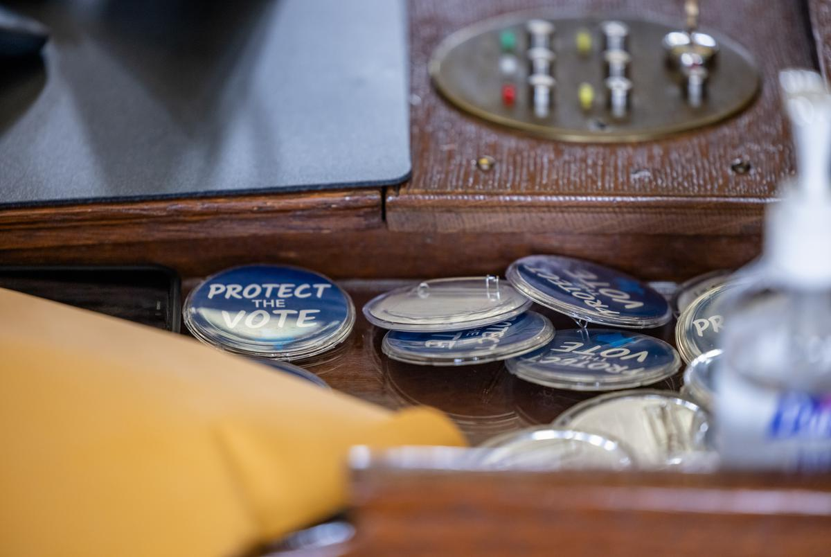 State Rep. Gene Wu, D-Houston, handed out buttons to his colleagues that read 'Protect the Vote' as the House prepares to debate controversial election legislation on May 30, 2021.