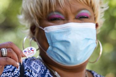 """Pinkie Powell shows off her """"I Voted"""" sticker after casting her ballot at the Bayland Community Center during the first day of early voting in Houston on Oct. 13, 2020. Powell says she didnít mind the hour way in line because """"it's time for my voice to be heard."""""""
