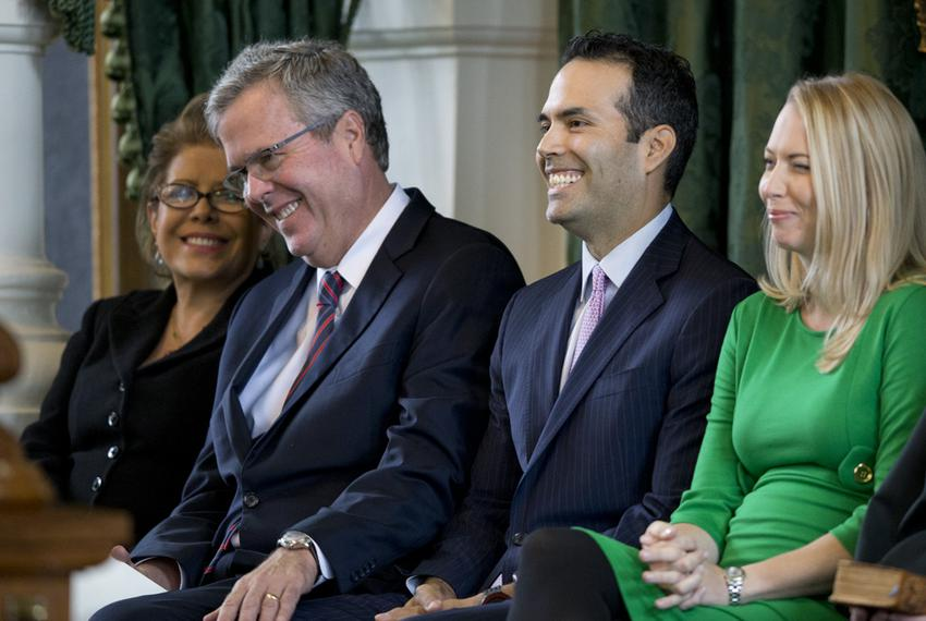 Jeb Bush puts his hand on his son George P. Bush's knee during a light moment in the younger Bush's swearing-in ceremony on …