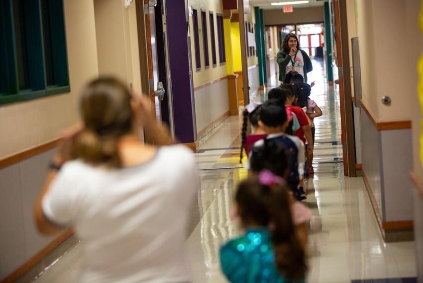 "Instructor's Aid, Nicole Johnson, walks JoAnn Zavala's pre-K students down the hall to music class, their first ""specials""..."