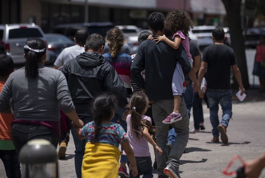 Volunteers usher a group of migrants to the Catholic Charities Humanitarian Respite Center across the street from the bus station in McAllen.