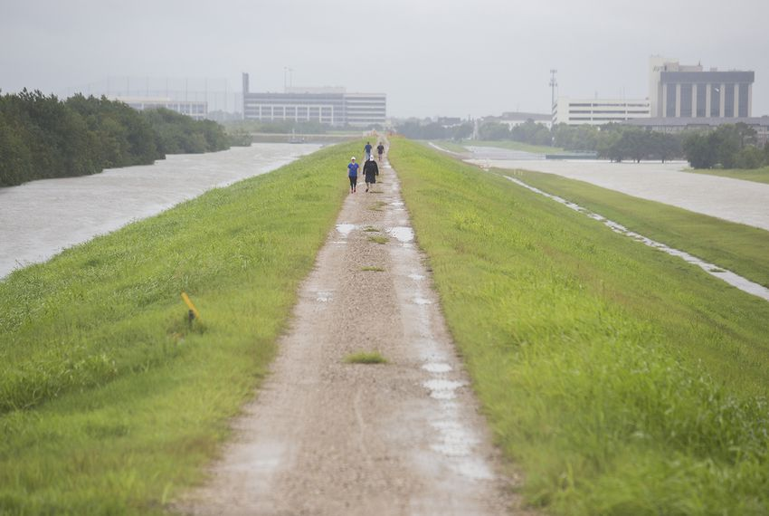 People walk along the Barker ReservoirDam in Houston on Tuesday, Aug 29, 2017. Torrential rains from Hurricane Harvey caused the U.S. Army Corps of Engineers to release water from the reservoir, aggravating flooding in neighborhoods below the dam.