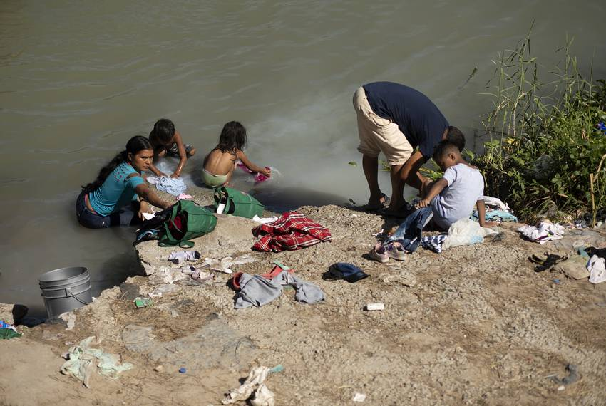 A group of migrants wash clothes on the banks of the Rio Grande in Matamoros, Tamaulipas on Oct. 16, 2019.