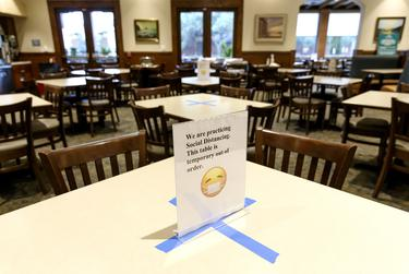 Social distancing signs mark tables as the Cleburne Cafeteria prepares to reopen for business.