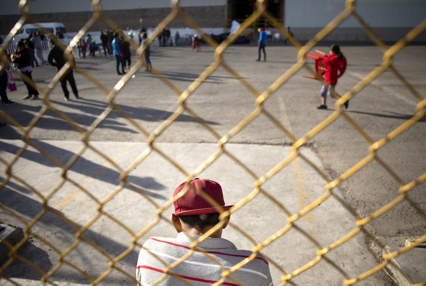 A young boy sits by the fence of the migrant shelter in Piedras Negras, Coahuila. A week before, the shelter held an estimat…