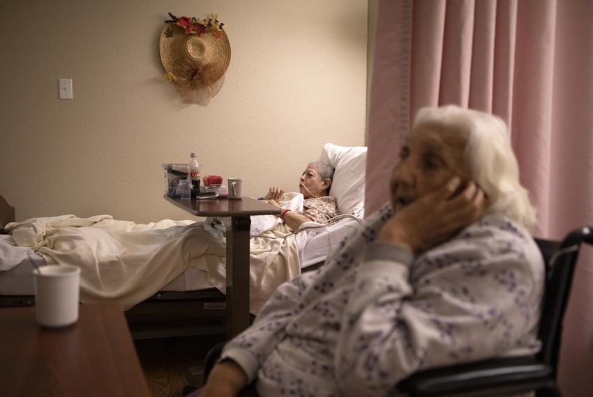 Rosa Ramos and Rebecca Pargas watch television while drinking coffee at the Amistad Nursing and Rehabilitation Center on Apr…