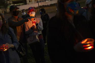 Wei Lin shields the flame of Marina Liu's candle during a rally and vigil held at the Grassy Knoll in Dallas in solidarity with the Asian community. The rally denounced racism and attacks on Asian Americans, and honored the victims of the shootings in Atlanta. March 21, 2021.