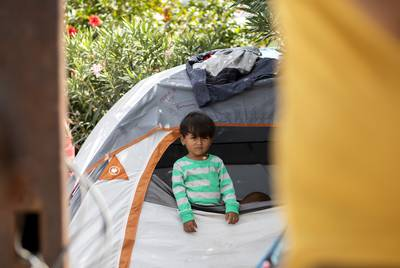 A young boy looks out of tent at the migrant camp near the Gateway International Bridge in Matamoros, Tamaulipas. Oct. 16, 2019.