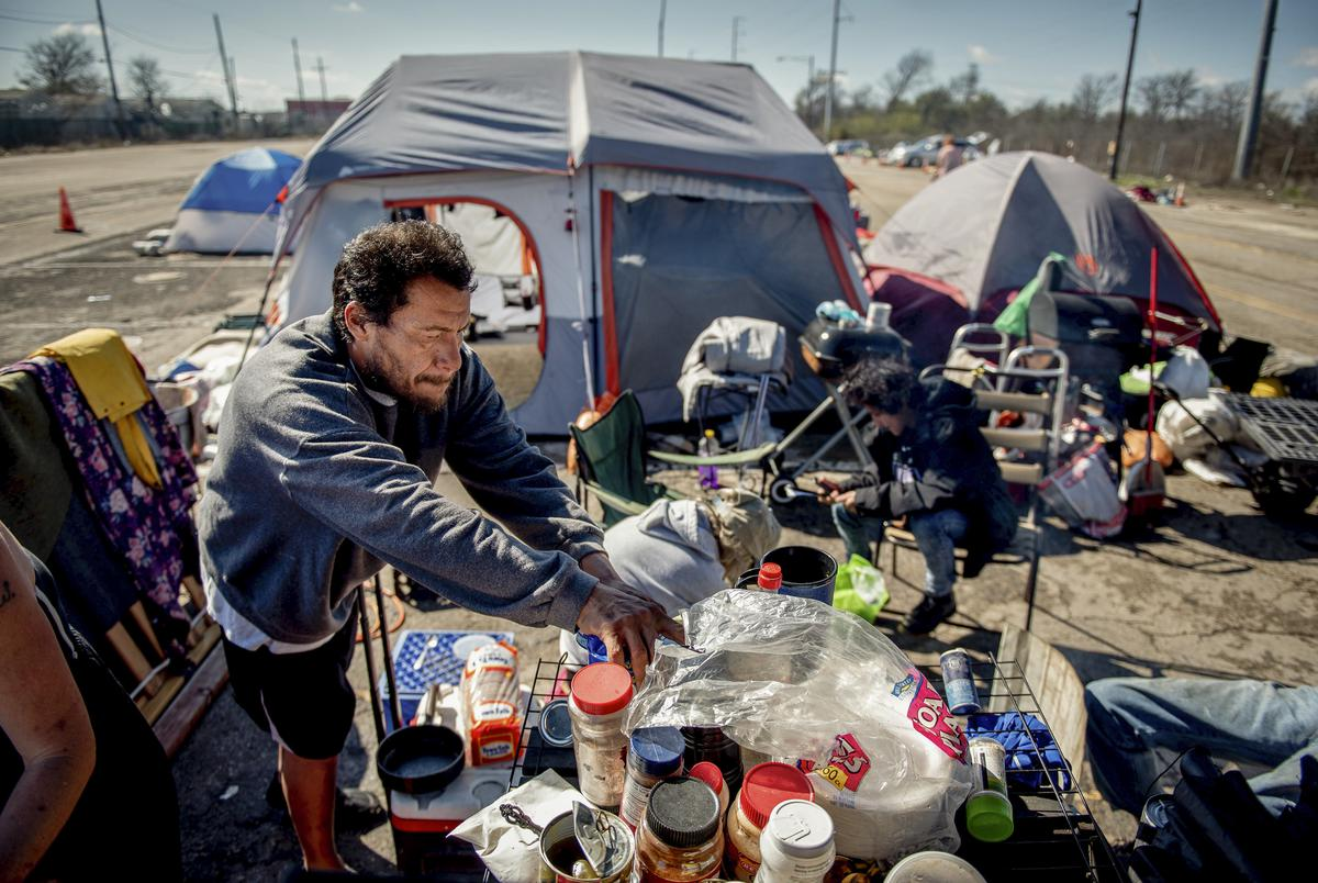 Manuel Baez helped prepare a meal at the state-sanctioned camping site in Austin in January.
