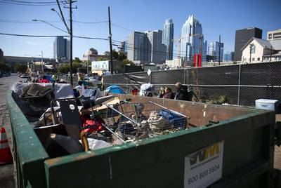 A dumpster sits next to a homeless camp on Neches Street in downtown Austin on Monday.