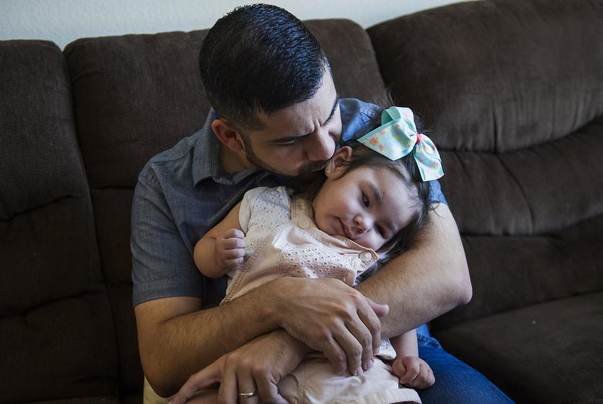 Emmanuel Garza holds his daughter Madelynn, 1, while she experiences a seizure Tuesday, June 13, 2017 at their home in Aur...