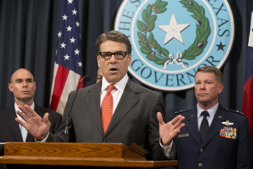 Gov. Rick Perry, flanked by State Rep. Dennis Bonnen, R-Angleton, and Texas Adjutant General John Nichols, announces the d...