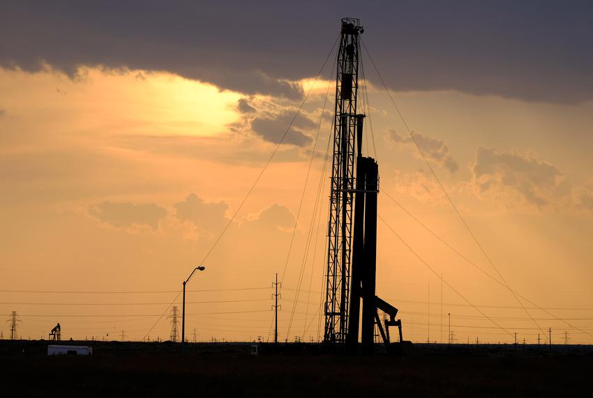 A drilling rig at sunset operates a couple hundred yards north of Fasken Elementary School on the north side of Midland, Tex…