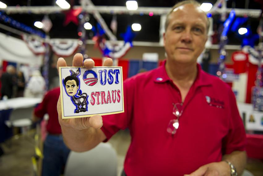 "Mike Zapp of Burleson, TX holds an ""Oust Straus"" sticker at the Tea Party booth at the state Repulblican Convention on Jun..."