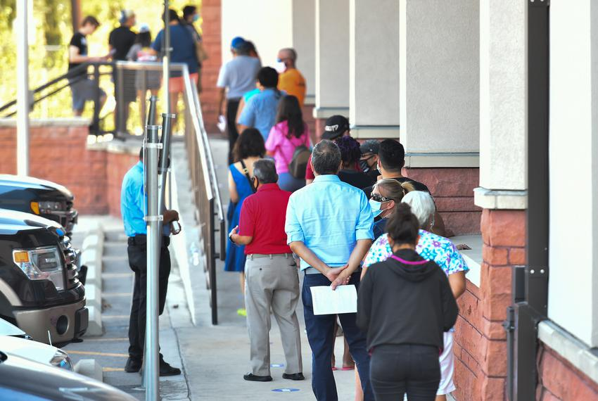 People wait outside the Bexar County Elections Department in San Antonio to drop off their mail-in ballots, voter registrati…