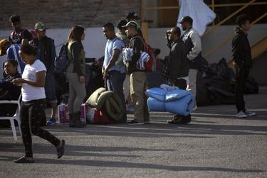 Migrants wait in line with their belongings inside the shelter. Individuals with Mexican visas are allowed to leave the facility and relocate to various cities in Northern Mexico.