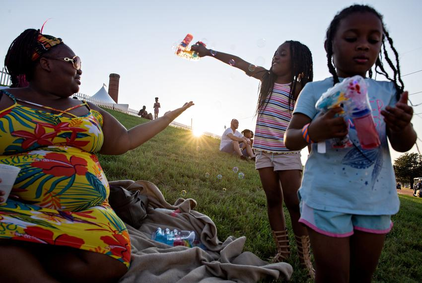 """Brianna Williams plays with her daughters Hope and Faith during the """"I Am Juneteenth"""" festival at the Panther Island Pavilio…"""