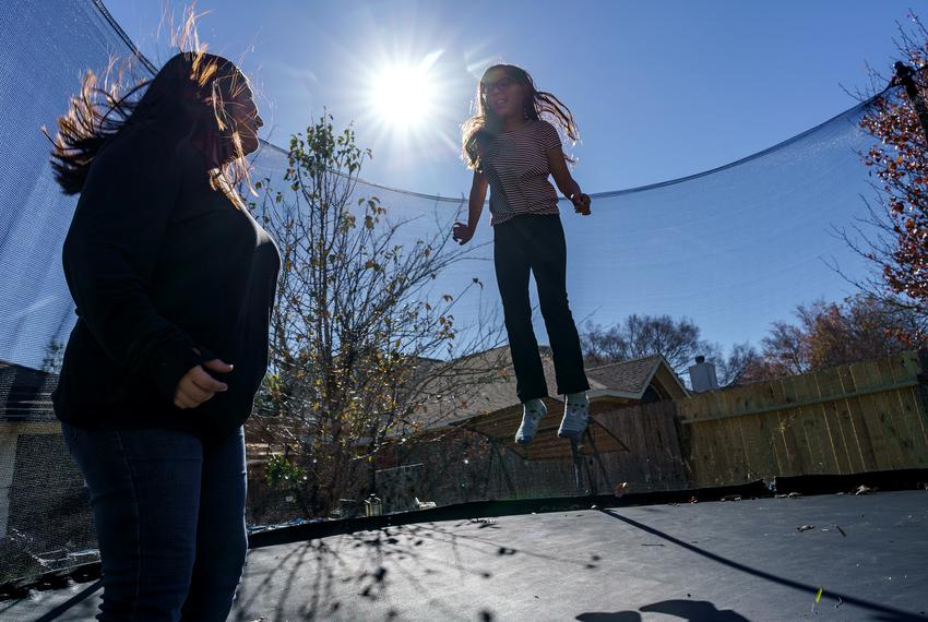 Isabel Suarez, left, and her sister, Llana Ramos, right, take a break from their virtual schooling to jump on the trampline …