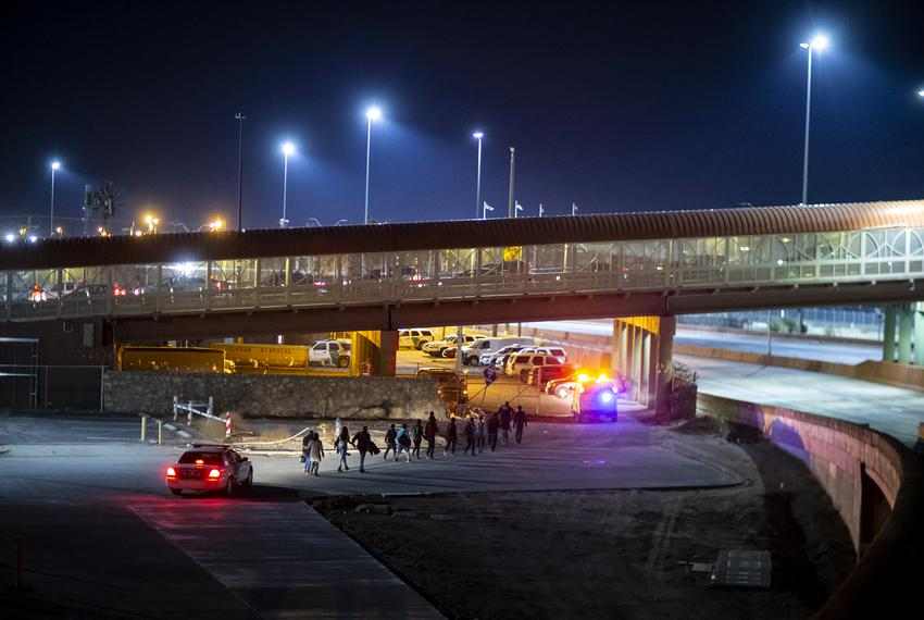A group of migrants are escorted by CBP agents near the Paso del Norte International Bridge in El Paso on June 15, 2019.