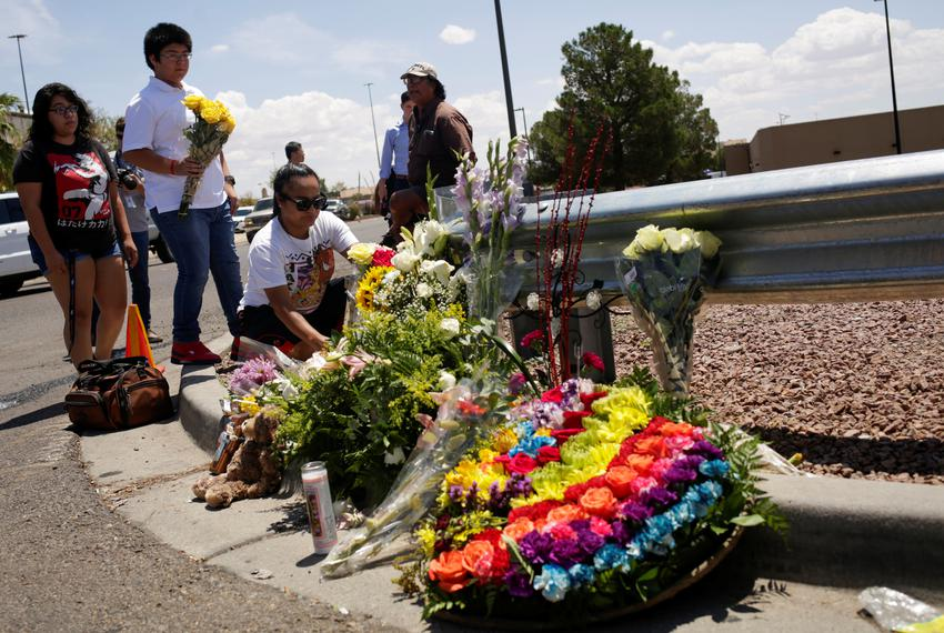 People place flowers at the site of a mass shooting where 20 people lost their lives at a Walmart in El Paso, on August 4,...