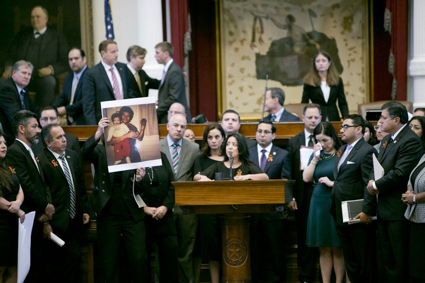 """State Rep. Veronica Neave, D-Dallas, gives an emotional speech as a picture of her father is held up during the debate on SB4 — the """"sanctuary cities"""" bill — on April 26, 2017."""