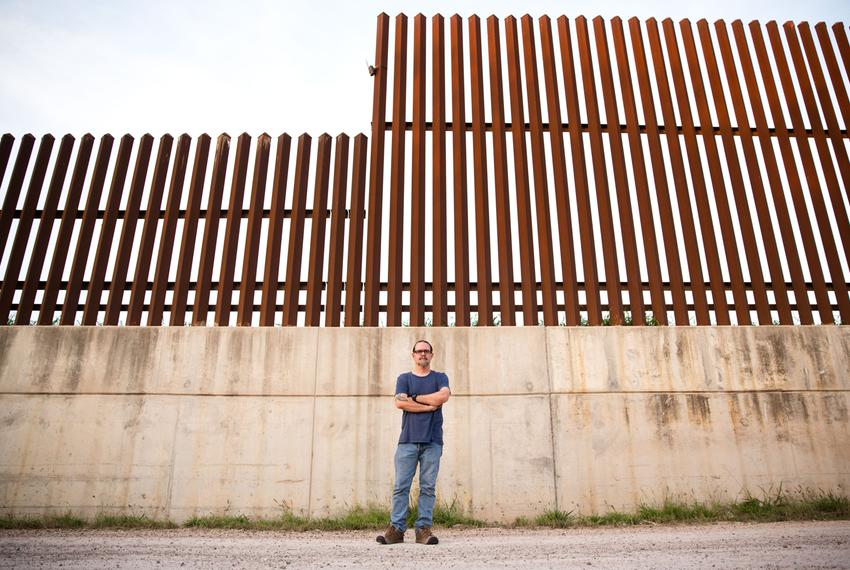 Scott Nicol, co-chair of the Sierra Club's Borderlands Campaign, stands in front of a concrete levee topped by the border fe…